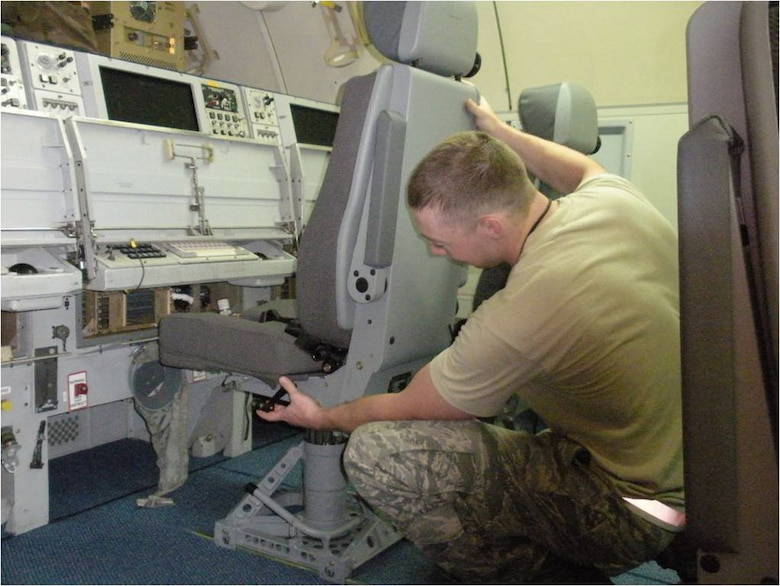 A maintenance crewmember at Tinker Air Force Base, Okla., installs a new operator stations seat aboard an E-3 Sentry recently. The new seats are expected to help alleviate back and neck stress for crews on long-duration missions. (Courtesy photo)