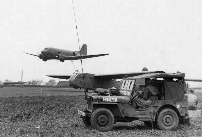 Making a low pass over the field, the C-47 has its hook dropped to snatch the CG-4 glider as controllers watch from their jeep. (U.S. Air Force photo)