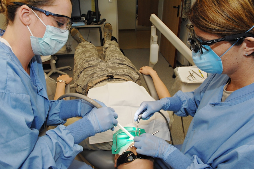 SPANGDAHLEM AIR BASE, Germany – Lt. Col. (Dr.) Holly Ellenburger (right) and Airman Amy Williams (left), both from the  52nd Dental Squadron, repair a cavity in the mouth of Senior Airman Mica Smith, 606th Air Control Squadron, Aug. 24. (U.S. Air Force photo/Senior Airman Benjamin Wilson)