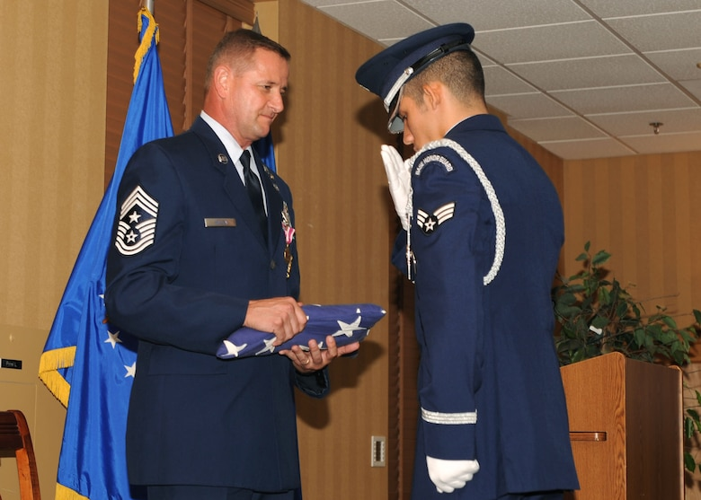 DAVIS-MONTHAN AIR FORCE BASE, Ariz. -- Chief Master Sgt. Lloyd Hollen (left), 12th Air Force (Air Forces Southern) command chief, recieves the colors during his retirement ceremony here Aug 14.  Chief Hollen retired after nearly 29 years of active service.  (U.S. Air Force photo by Airman 1st Class Brittany Dowdle)