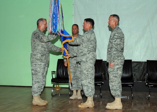 Maj. Gen, Ronald R. Ladnier (left), commander of 17th Air Force (Air Forces Africa), accepts the 449th Air Expeditionary Group flag from outgoing commander Col. John Brunhaver (center) during a change of command ceremony at Camp Lemonier, Djibouti Aug. 26. Waiting to accept the flag is incoming commander Col. Jon Ullmann (right) as 449th Command Chief Master Sergeant Bradlee Farrin assists. Colonel Ullmann is normally the Combat Operations Division Director for 17 AF's 617th Air Operations Center, located at Ramstein Air Base, Germany. Col. Brunhaver returns to Air Mobility Command at Scott AFB, Ill., where he is the Division Chief for the Expeditionary Mobility Operations Division. (USAF photo by Master Sgt. Jim Fisher)