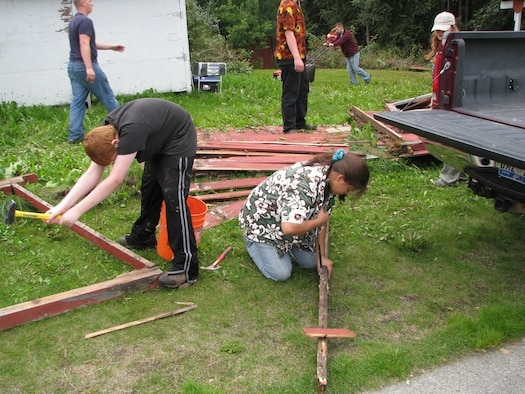 ELMENDORF AIR FORCE BASE, Alaska -- The volunteer group finishes demolishing and removing nails from the remnants of the old fence and begins mowing the back yard and starting demolition of the porch. The group gave their free time on Aug. 23 and 24 to help out an Air Force Guardsman and her family. (courtesy photo)