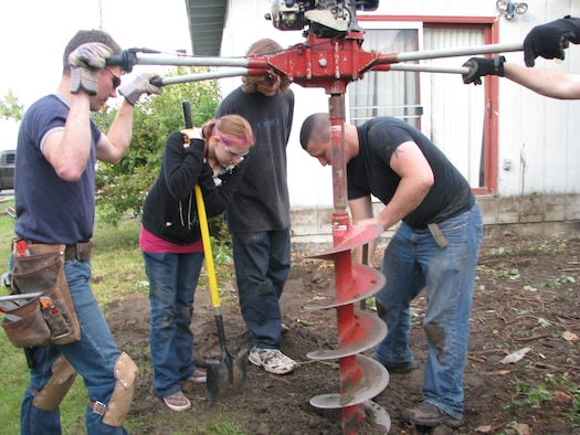 ELMENDORF AIR FORCE BASE, Alaska -- Members of a volunteer group drill new footings that will hold up the new porch to Tech. Sgt. Mary Bramer house. Bramer is the widow of Tech. Sgt. Mark Bramer who died in the Yukla 27 crash. (courtesy photo)