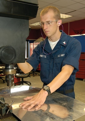 Petty Officer 3rd Class John Barnette pre-drills holes in sheet metal.  Maintainers manufacture doublers to reinforce areas as needed. (Air Force photo by Margo Wright)