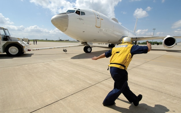Moving a Navy E-6 out of a VQ-4 maintenance hangar and onto the ramp is a careful process directed by Airman Daniel Flores. (Air Force photo by Margo Wright)