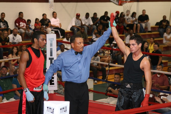 Above, referee Mike Walker raises the hand of James Barber, who won a unanimous decision over Army Reserve boxer Tim Berna. Barber is the reigning base champion.(Air Force photo by Becky Pilifant)