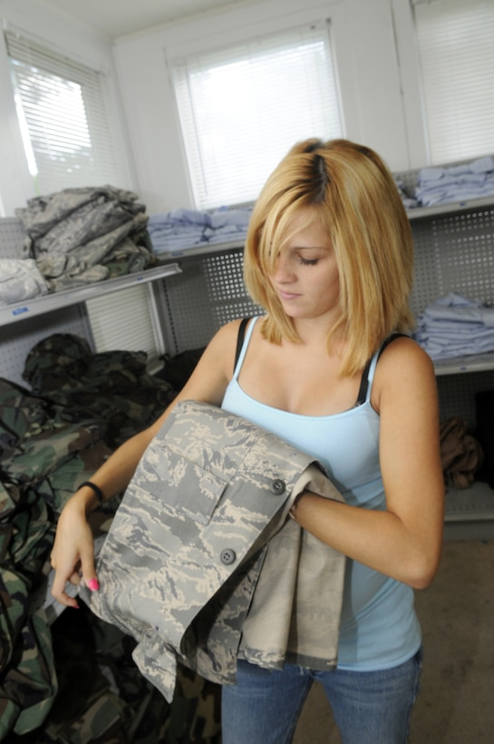 Katrina Green, Airman's Attic volunteer, folds one of many uniforms available at the facility. U. S. Air Force photo by Sue Sapp