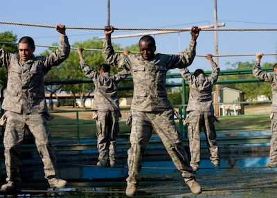 trainees swing from the monkey bars as they clear their last obstacle ...