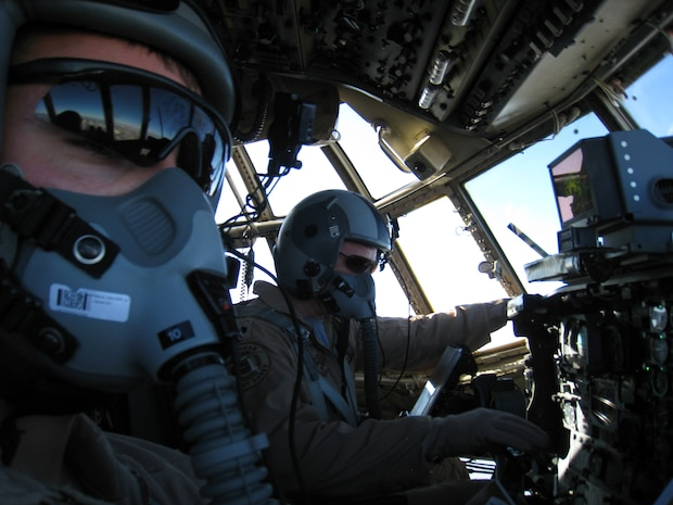 BAGRAM AIRFIELD, Afghanistan - Lt. Col. Tommy Atkinson (right) pilots a C-130H Hercules over Northern Afghanistan on a humanitarian airdrop mission. The Airmen of the 774th Expeditionary Airlift Squadron have been dropping an average of five to eight tons of supplies and equipment per mission to Coalition forces and Afghan civilians in support of Operation Enduring Freedom. (U.S. Air Force photo)