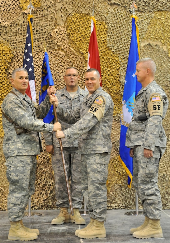 SATHER AIR BASE, Iraq, -  Lt. Col. Steven Painter, outgoing 447th Expeditionary Security Forces Squadron commander, passes the 447th ESFS guiedon off to Col. Pat Savoy, 447th Air Expeditionary Group commander, here Aug. 26.  Colonel Painter is from the Pennsylvania Air National Guard 171st Air Refueling Wing in Pittsburgh.  (U.S. Air Force photo / Staff Sgt. Misty D. Slater)