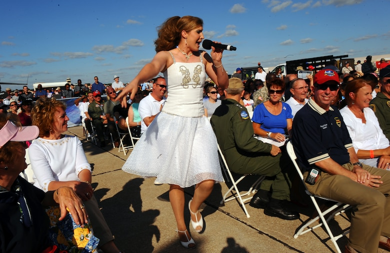 """OFFUTT AIR FORCE BASE Neb. -- Staff Sgt. Naomi Keen, a vocalist with Tops in Blue, entertains a large crowd during a performance at the 2009 Defenders of Freedom Open House and Air Show here Aug. 29. Tops in Blue, also known as the Air Force's expeditionary entertainers, performed numerous songs during the show including """"Neon Rainbow,""""  """"Chicken Fried"""" and """"God Bless the USA.""""  U.S. Air Force Photo by Josh Plueger"""