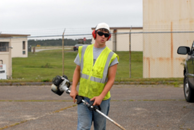 Rylan Richard, 16, prepares to trim the curb side grass outside Building 158 as a Pavement and Grounds summer hire. (U.S. Air Force Photo/Staff Sgt. Kerri Cole)