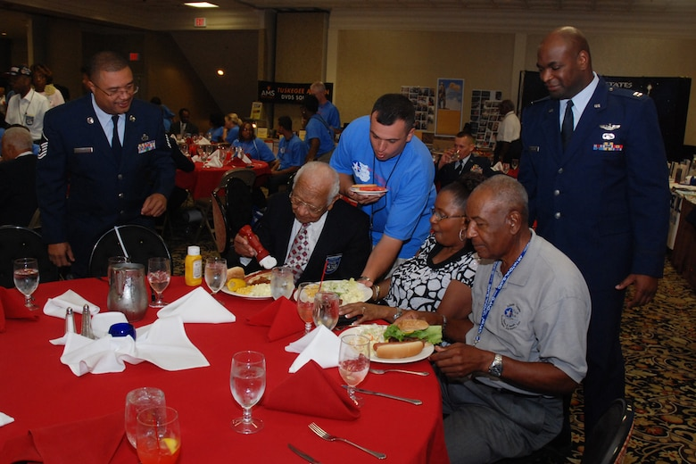 Master Sgt. Floyd Stanfield (left), 94th Maintenance Group and president of the Atlanta Tuskegee Airman, Inc. Chapter, Master Sgt. John Alsvig (in blue), 56th Fighter Wing first sergeant and Capt. Darrell Bogan (right), 94th Airlift Wing equal opportunity officer, serves Wilbur G. Mason and Edgar Lewis of the TAI Atlanta Chapter and Naomi Sport, widow of original Tuskegee Airman Vernon Sport at the 2009 Tuskegee Airman National Convention student luncheon Aug. 8. (U.S. Air Force photo/Tech. Sgt. James Branch)