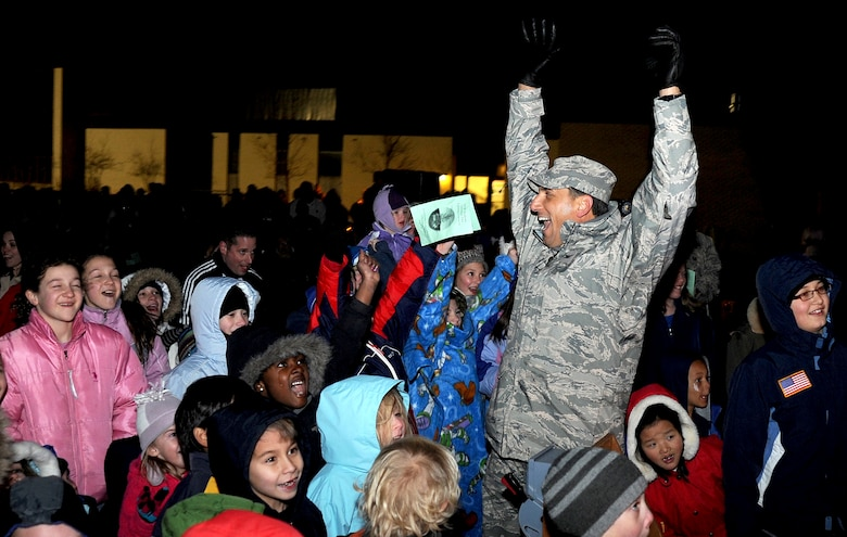 Col. Rick LoCastro and children cheer as Santa Claus arrives at the Community Center Chapel during a Christmas tree lighting ceremony Dec. 1, 2009. More than 200 people attended the event. Colonel LoCastro is the 10th Air Base Wing commander. (U.S. Air Force photo/Johnny Wilson)