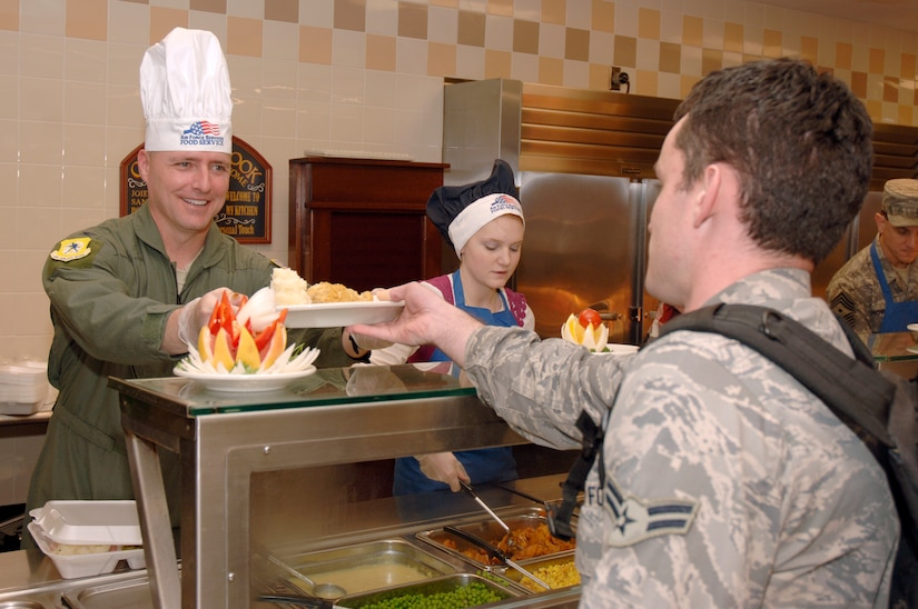 Col. John Wood serves Airman 1st Class Joe Pears a plate of food during the Thanksgiving dinner held at the Robert D. Gaylord Dining Facility here Nov. 26. A traditional Thanksgiving dinner with turkey, ham and all the fixings were served to active-duty military and their families. Colonel Wood is the 437th Airlift Wing commander and Airman Pears is a passenger service agent with the 437th Aerial Port Squadron. (U.S. Air Force photo/Staff Sgt. Marie Brown)