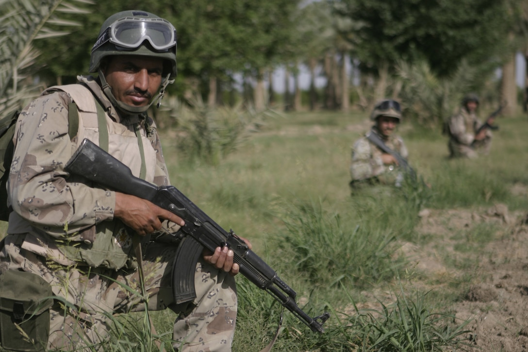 SAQLAWIYAH, Iraq - Iraqi soldiers with the Iraqi Security Forces' 2nd Company, 2nd Battalion, 2nd Brigade provide security in a field outside Saqlawiyah May 22.  The Iraqi soldiers worked alongside Company A, 1st Battalion, 6th Marine Regiment personnel and combat engineers to sweep through numerous farm fields outside Saqlawiyah, looking for hidden weapons caches and insurgent activity.
