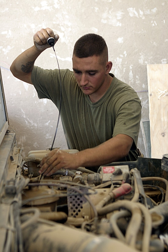 CAMP BAHARIA, Iraq - Lance Cpl. Michael Banks, a vehicle mechanic with 2nd Platoon, Truck Company, Headquarters Battalion, 3rd Marine Division, inspects the oil level on a High Mobility Multi-Wheeled Vehicle inside the maintenance bay here.  The Truck Company vehicle mechanics and operators, originally from Okinawa, have been working alongside 1st Battalion, 6th Marine Regiment personnel in and around Fallujah since mid-March, accomplishing tasks such as servicing vehicles, conducting supply and logistics convoys, and transporting the infantrymen around the city.
