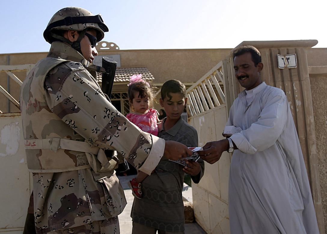 Hit, Al Anbar, Iraq (August 6, 2005)--An IIF soldiers hands out handbills during a patrol. (Official USMC Photo by Corporal Ken Melton)