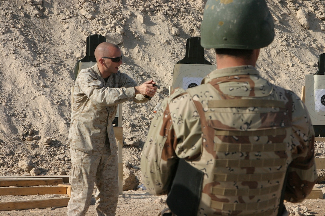 CAMP HABBANIYAH, Iraq - Sergeant Peter K. McKinney, the chief instructor for Personal Security Detail Development course, demonstrates how the aim of a pistol is thrown off by anticipating the discharge of the weapon.