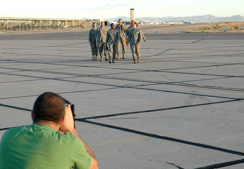 ANG Creative Team photographer Rob Trubia takes photographs of 162nd Fighter Wing members at Tucson International Airport, Dec 3. (From the left) Staff Sgt. Brandy Guzman, Tech. Sgt. Bruce Newcomb, Staff Sgt. Erin Peters, Staff Sgt. Mark Catlin, Master Sgt. Gary Jack and Staff Sgt. Robin Hinton were among 20 unit members featured in the four-day photo shoot. The images will be used in brochures intended to attract recruits with prior active duty military experience. (Air Force photo by Maj. Gabe Johnson)