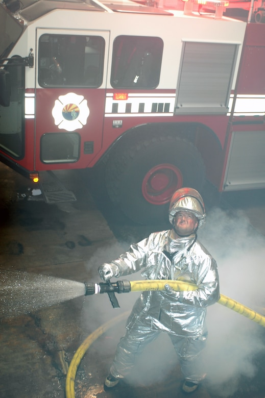 Staff Sgt. David Arneson simulates putting out a fire in the base fire station Dec. 2. The demonstration was photographed for use in brochures intended to attract recruits with prior active duty military experience. (Air Force photo by Maj. Gabe Johnson)