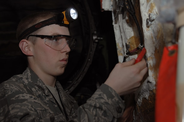 Airman Mattox Davis, 509th Maintenance Squadron Aerospace Propulsion Apprentice, removes fastblock, a flame resistant coating,  so the panel can be removed to access the damaged tail pipe.  (U.S. Air Force photo by Senior Airman Jessica Mae Snow) (Released)