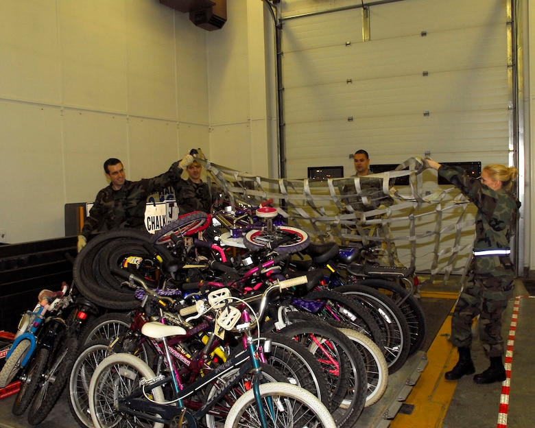 (Left to right) Alaska Air Guardsmen Staff Sgt. Woody Miller, Senior Airman John Darnall, Senior Airman Ryan Pierce and Tech. Sgt. Summer Rehak from the 176th Logistics Readiness Squadron pulls a top net over a pallet of refurbished bicycles on December 6, 2009. The bikes will be airlifted by the Alaska Air National Guard?s144th Airlift Squadron, to Afghanistan to be given to disadvantaged children. (Alaska Air National Guard photo by Tech. Sgt. Shannon Oleson)