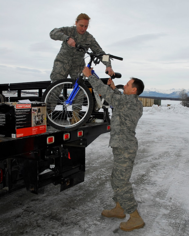 Alaska Air Guardsman Master Sgt. Tess Walsh hands Senior Master Sgt. Thomas Martin a bicycle from the truck bed on December 5, 2009. Walsh and Martin are from the 176th Logistics Readiness Squadron, Alaska Air National Guard, Anchorage, Alaska. The bicycle and twenty-two other refurbished bikes will be airlifted by the Alaska Air National Guard?s144th Airlift Squadron, to Afghanistan to be given to disadvantaged children. (Alaska Air National Guard photo by Tech. Sgt. Shannon Oleson)