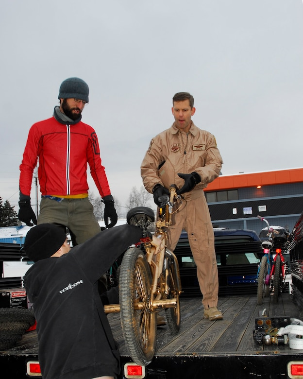 Adam Cosic watches as Henry Crankshaw hands Alaska Air Guardsman Lt. Col. David Glick a bicycle to load onto the truck bed on December 5, 2009.  Cosic and Crankshaw are volunteers at Off the Chain, a bicycle collective, in Anchorage, Alaska.  Glick is a pilot with the 144th Airlift Squadron, Alaska Air National Guard.  The bicycle and twenty-two other refurbished bikes will be airlifted to Afghanistan to be given to disadvantaged children. (Alaska Air National Guard photo by Tech. Sgt. Shannon Oleson)