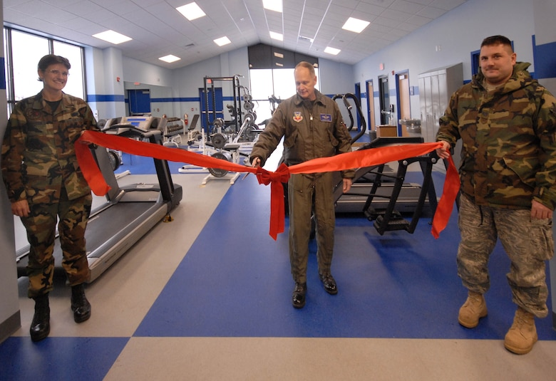 Master Sgt. Carmen LaGuardia, left, and Tech. Sgt. Craig Madden, right , holds the ribbon as Col. Rodger Seidel prepares to cut it during opening ceremonies for the new base gym Friday, Dec, 4, 2009.  The new facility feature more equipment for airman to prepare for the new Air force fitness requirements. (Photo by Master Sgt. Dale Atkins)