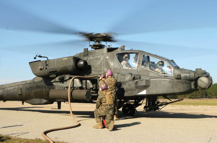 Lance Cpl. Kel Clark::r::::n::Air operation Marines with Marine Wing Support Squadron 273 conduct hot fuels on an Army Apache at Fort Stewart Army Base in Hinesville, Ga., Dec. 7. The Sweathogs of MWSS-273 was aboard Fort Stewart for their yearly field training exercise called Battle Hog.