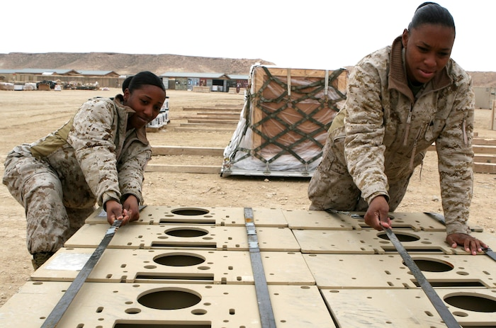 Cpl. Erica Brown (left), a procurement management cell supply clerk with Detachment B, 2nd Maintenance Battalion, Combat Logistics Regiment 27 (Forward), and Cpl. Candice Neille, a traffic management specialist with Det. B, ensure that materials are properly secured before being loaded and transported to the flight line aboard Al Asad Air Base, Iraq, for redistribution Dec. 8, 2009.  The detachment of Marines from 2nd Maintenance Battalion stayed past their unit's redeployment in order to continue working toward the Marine Corps' mission of retrograding gear and equipment from Iraq.  (U.S. Marine Corps photograph by Lance Cpl. Melissa A. Latty)