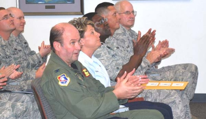 507th Air Refueling Wing and 35th Combat Communications Squadron members respond with applause as they hear the outbrief good news.