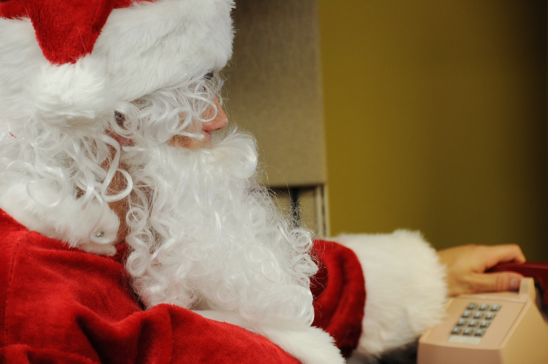 """Santa picks up another call on the """"Santa Hotline"""" to talk with boys and girls before he makes his holiday journey.  The """"Hotline"""" will be active Dec. 14-18 from 5 p.m. to 9 p.m.  Children of all ages wishing to call in with last-minute holiday wishes can call 850-882-NOEL (6635).  (Air Force photo/ Samuel King Jr.)"""