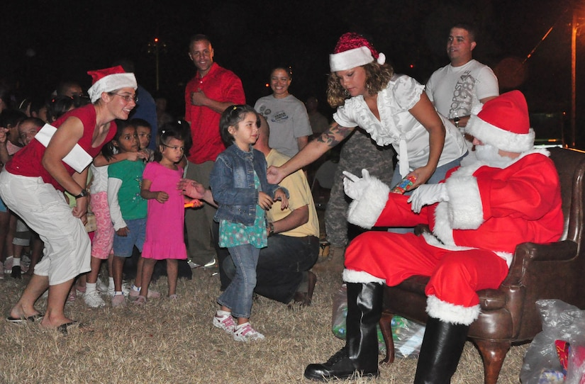 """SOTO CANO AIR BASE, Honduras – Santa Claus hands out presents and candy to children from a local orphanage Dec. 1 in front of the base Christmas tree near Building B-202. The children were brought on base for the tree-lighting ceremony. After the tree lighting they sang some Christmas carols, listened to the reading of """"A Christmas Story"""" and had a surprise visit from Santa Claus, who handed out presents and candy to all the children (U.S. Air Force photo/Staff Sgt. Chad Thompson)."""