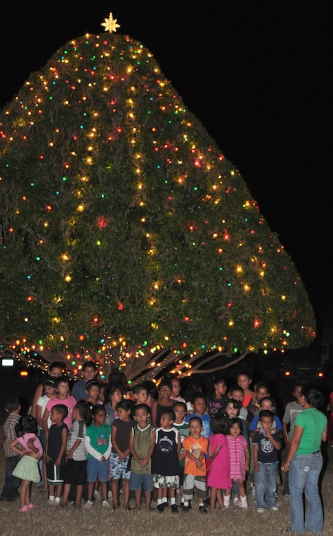 """SOTO CANO AIR BASE, Honduras – About 40 children from a local orphanage sing """"Joy to the World"""" Dec. 1 in front of the base Christmas tree near Building B-202. The children were brought on base for the tree-lighting ceremony. After the tree lighting they sang some Christmas carols, listened to the reading of """"A Christmas Story"""" and had a surprise visit from Santa Claus, who handed out presents and candy to all the children (U.S. Air Force photo/Staff Sgt. Chad Thompson)."""
