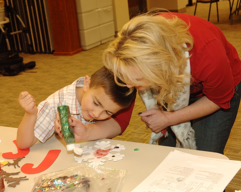BUCKLEY AIR FORCE BASE, Colo. -- Gidget Barela shows her son Chance how to apply glue glitter to a snowflake during the Deployed Spouses Family Dinner at the Chapel Annex Dec. 4. (U.S. Air Force photo by Tech. Sgt. Shirley Henderson)