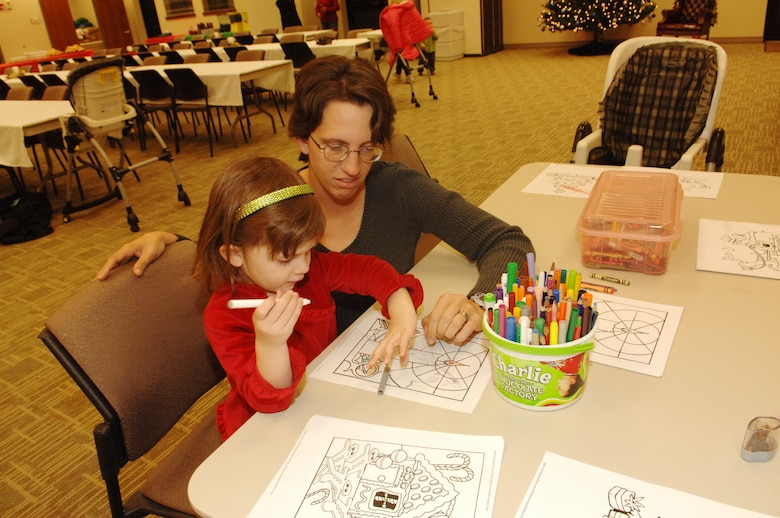 BUCKLEY AIR FORCE BASE, Colo. -- Desiree Bradley helps her daughter Jessica color during the Deployed Spouses Family Dinner at the Chapel Annex Dec. 4. (U. S. Air Force photo by Tech. Sgt. Shirley Henderson)