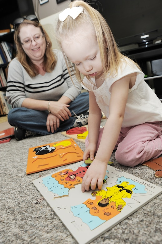 McConnell family member Savannah Holmes plays with a puzzle Nov. 25, 2009, while Stephanie Shellenbarger observes her motor skills at McConnell Air Force Base, Kan. The Parents as Teachers Heroes at Home parent educator program offers servicemembers, military spouses and expecting mothers family support and education for their children before they enter kindergarten. Ms. Shellenbarger is a PAT-HAH educator. (U.S. Air Force photo/Tech. Sgt. Chyrece Campbell)