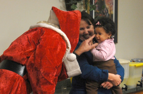 Santa Claus visits with a child during the Hearts Apart annual holiday party Dec. 4 at the Hurlburt Field Chapel. Throughout the year, the program sponsors a series of monthly gatherings for spouses and children of deployed members. (Air Force photo by Senior Airman Matthew Loken)