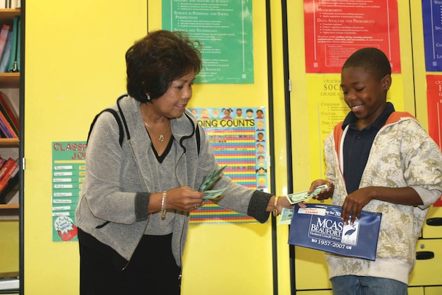 Ehmma Beach, a social studies and Language Arts teacher and the creator of the Beach Bucks program at Bolden Elementary school aboard Laurel Bay, passes Tom Powell, a sixth grade student at Bolden Elementary school Beach Bucks for good behavior.