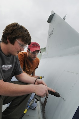 Joshua Player and Travis Lockerman work on a panel repair on an F-102 at the Museum of Aviation restoration hangar. U. S. Air Force photo by Sue Sapp