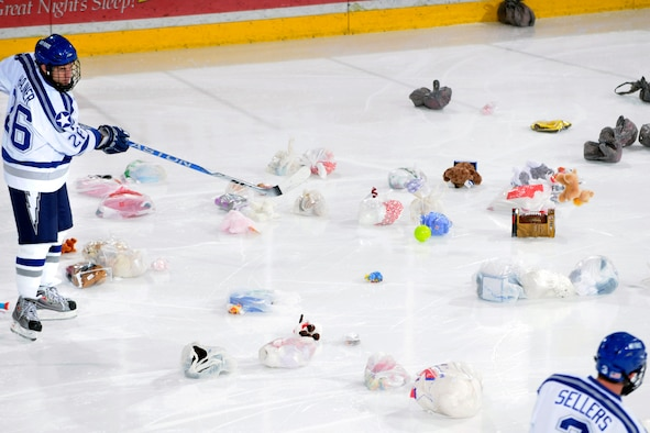 "Falcons forward Jeff Hajner and defender Brad Sellers rein in toys from the ""Toy Trick"" after the Falcons scored their first goal of the game against American International College Dec. 5, 2009, at the Air Force Academy's Cadet Ice Arena. The Falcons have distributed more than 5,000 toys to children in local hospitals and clinics during the Toy Trick's 10 years of operations. Hajner, a senior, is from Las Vegas. Sellers, a junior, is from Centenniel, Colo. (U.S. Air Force photo/J. Rachel Spencer)"