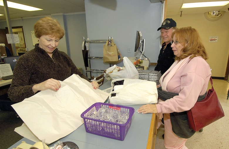 Retired Army family Bill and Karen Philpott, of Fairland, take advantage of a visit to their Sailor son serving in the Fleet Air Reconnaissance Squadron THREE to pick up some bargains. Susan Foster, a 17-year volunteer, wraps the couple's purchases at check out. The couple said they always hope their visits correspond with the days the shop is open. ( Air Force photos by Margo Wright )