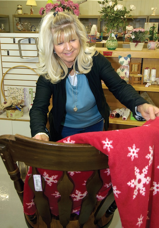 Tinker Thrift Shop volunteer Janie Hardin makes a holiday throw and a wooden rocker more inviting for potential shoppers in the thrift shop's furniture area recently.  Ms. Hardin consigned items for years then became a volunteer in the shop more than four years ago. (Air Force photos by Margo Wright )