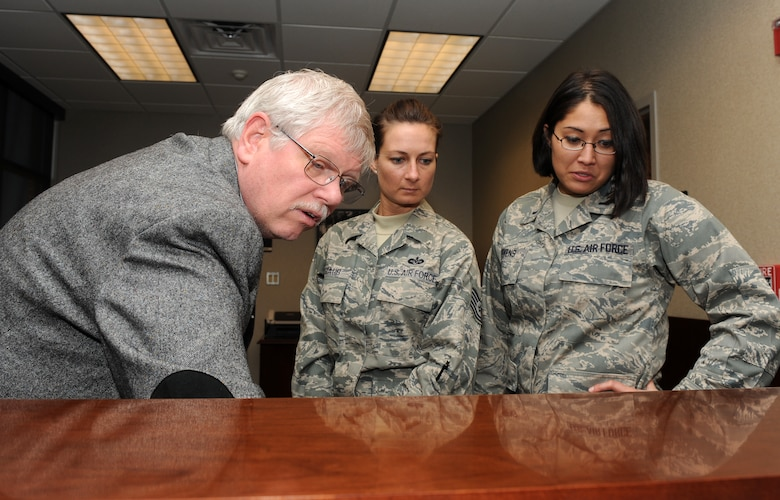LANGLEY AIR FORCE BASE, Va. --  David Moorhouse, 1st Mission Support Group Joint-Basing office coordinator, shows Tech. Sgt. Rachel Staub, 1st Fighter Wing Command Chief's assistant, and 1st Lt. Karena Stevens, 1st Fighter Wing executive officer, how to utilize the upgraded phone system in the new 633rd Air Base Wing's building Dec. 9.  The 633d ABW will be holding its activation ceremony Jan. 7.  (U.S. Air Force photo/Senior Airman Zachary Wolf)