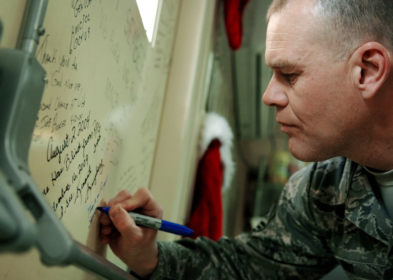 Chief Master Sgt. of the Air Force James A. Roy signs the warrior wall Dec. 4, 2009 at the Air Force Theater Hospital at Jooint Base Balad, Iraq. During his first visit to JB Balad as the chief master sergeant of the Air Force, Chief Roy toured various locations on the base and mentored Airmen during an Airman's call. (U.S. Air Force photo/Senior Airman Christopher Hubenthal)