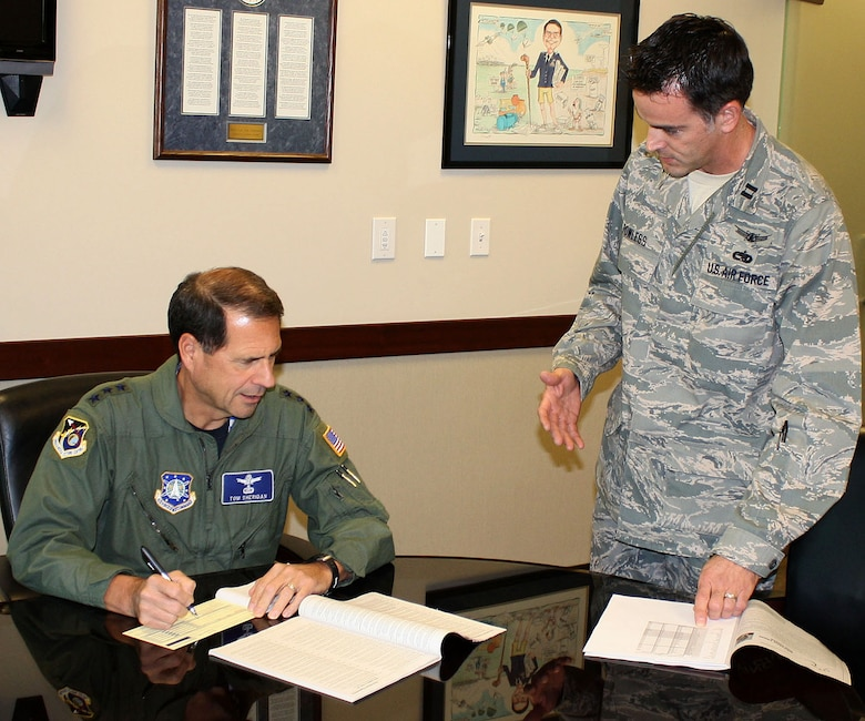 Lt. Gen. Tom Sheridan (left), Space and Missile Systems Center commander, fills out his 2009 Combined Federal Campaign contribution form, as CFC project officer Capt. Justin Powless, SMC Program and Integration, looks on, Dec. 4. As of week 4, the Los Angeles Air Force Base has made 100 percent contact and raised 51 percent of the contribution goal. This year's CFC campaign began Nov. 4 and ends on Dec. 15. For further information, contact Captain Powless at 310-653-1269. (Photo by 1st Lt. Matt Nelson)