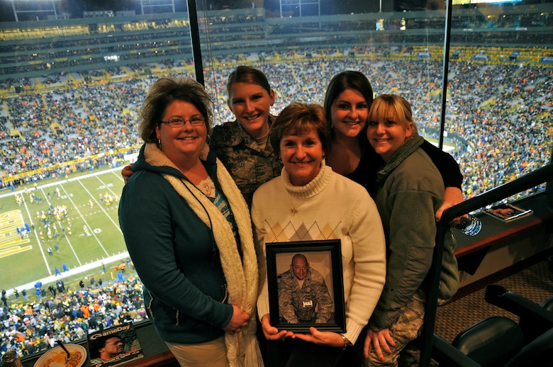 The Green Bay Packers honored military families during their recent Monday Night Football game against the Baltimore Ravens.  The Murray family was recognized at half-time on the 50-yard line at Lambeau Field and was surprised by a personal message from Lt. Col. David Murray, a nurse practitioner with the 115th Medical Group deployed to Balad Air Base, Iraq as a flight commander of the intermediate care ward at the Balad Theatre Hospital.  Theresa Murray holds a picture of her husband, David and attended the game with her four daughters (left to right) Jennifer Murray-Alston, Staff Sgt. Jamie Murray, Kelly McMeans and Staff Sgt Julie Murray who are all combat veterans, two of which are current members of the 115th FW.