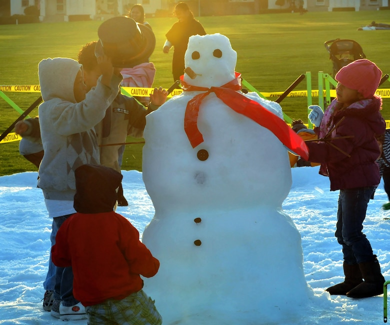 Children play in the snow during the Los Angeles Air Force Base Snow Day held at Fort McArthur, Dec. 4. More than 20 tons of man-made snow covered the children's play area and was part of the festivities surrounding the annual Tree Lighting Ceremony during the evening.  Other festivities included a visit from Santa, two 50-ft. sled runs and a holiday story reading by Col. Anita Latin, 61st Air Base Wing commander. (Photo by Atiba S. Copeland)